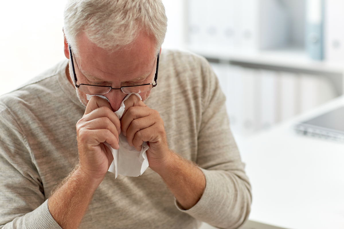 senior-man-blowing-nose-with-napkin-at-hospital-PKNY9ZW